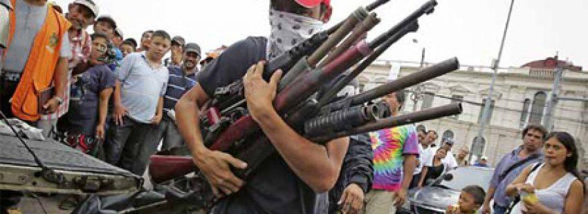 chico armado con varias escopetas y fusiles