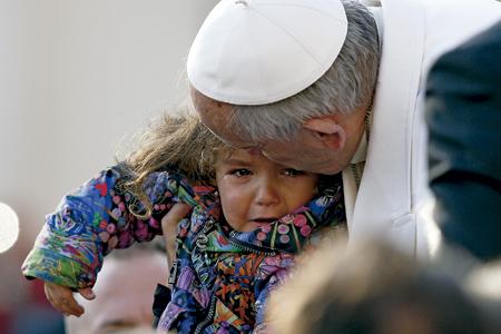papa Francisco abraza a una niña que está llorando
