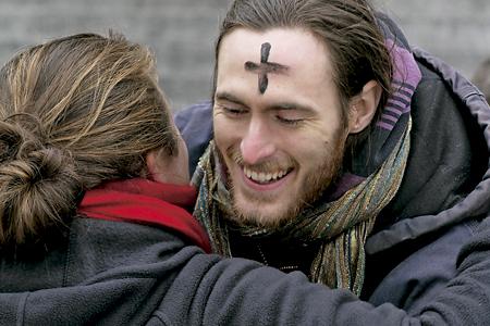 un chico con cruz de ceniza marca del Miércoles de Ceniza inicio Cuaresma abrazo con una chica