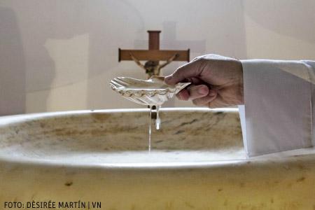 Juan Carlos Alameda, párroco de Tejina, Tenerife, en la pila bautismal con una concha con la que vierte agua. Foto Dèsirée Martín para VN