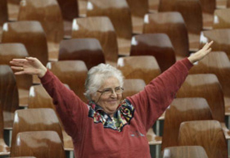 mujer de Iglesia sentada en una sala vacía sola abre los brazos en expresión de felicidad