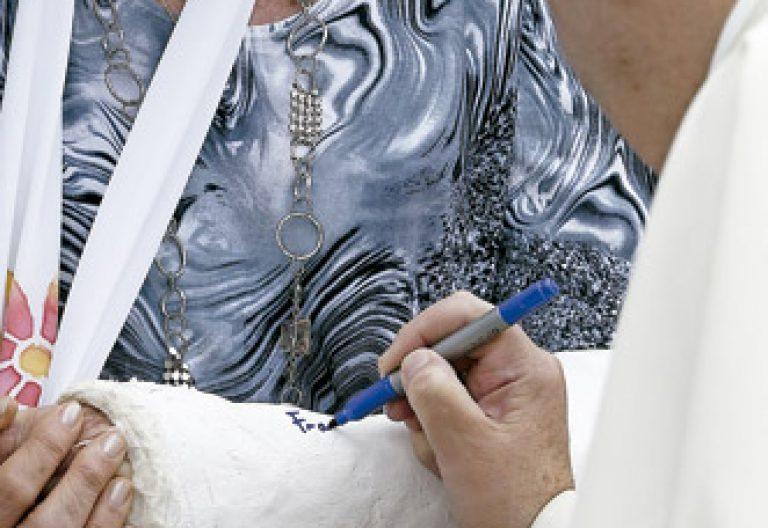 papa Francisco firma la escayola en un brazo a una mujer