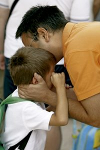 padre besa a un hijo que está llorando al recogerlo del colegio
