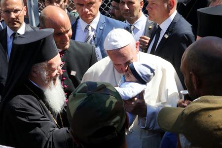 papa Francisco besa a un bebé de una familia de refugiados en el campo de Moria, Lesbos, en presencia del patriarca Bartolomé, 16 abril 2016