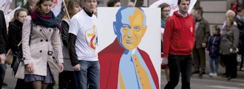 jóvenes participantes de la JMJ de Cracovia caminan por la calle con banderas y un cartel con la imagen de san Juan Pablo II