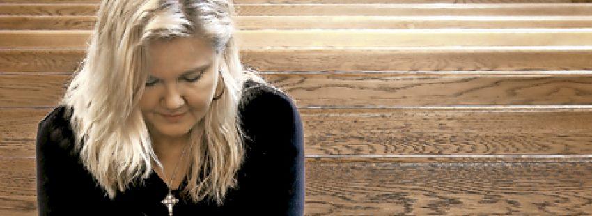 mujer sola sentada en los bancos vacíos de una iglesia