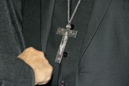 cruz pectoral crucifijo de un obispo vestido de negro