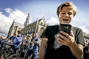 niño juega a Pokemon Go en la plaza central de Haarlem, Holanda