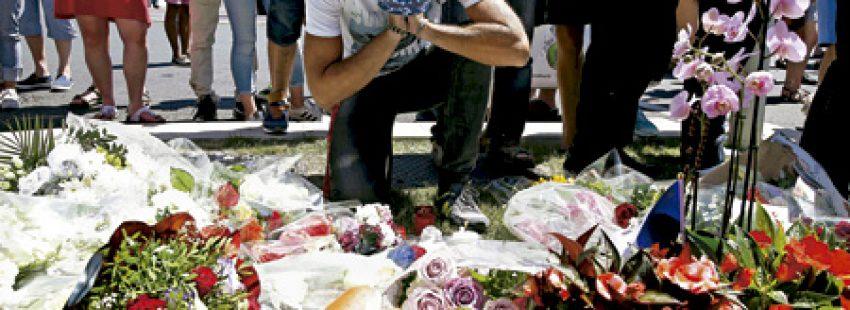 joven reza ante coronas de flores depositadas en el Paseo de los Ingleses, donde tuvo lugar el ataque en Niza 14 julio 2016