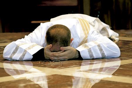 sacerdote rezando tumbado en el suelo
