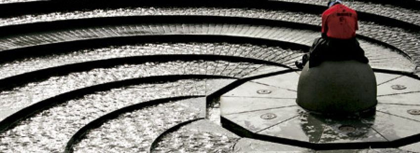 hombre rezando en una fuente de agua en forma de espiral