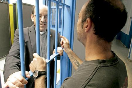 Florencio Roselló, director del departamento de Pastoral Penitenciaria de la CEE, conversa con un recluso a través de rejas
