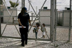 niñas iraquíes refugiadas hablando con una policía detrás de una valla en un centro de detención de inmigrantes en Grecia