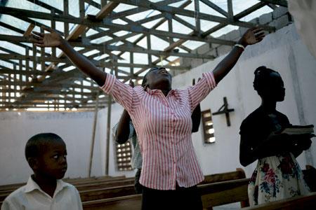 mujer reza en una iglesia devastada por el paso del huracán Matthew en Haití octubre 2016