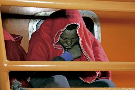 inmigrante llegado en patera a las costas de Europa recogido del mar y tapado con una manta