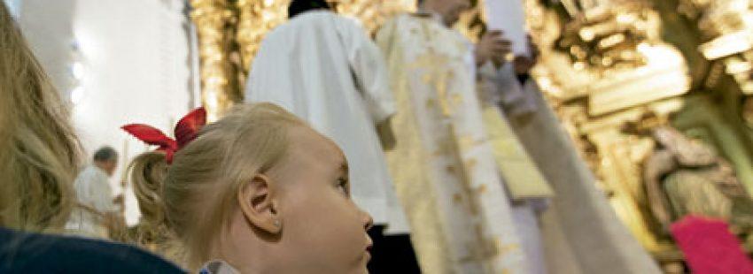 niña en brazos de su madre en una iglesia durante una misa con sacerdote