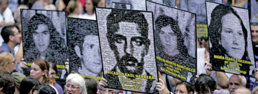 marcha ciudadana en Argentina con carteles con fotos de personas desaparecidas durante la dictadura