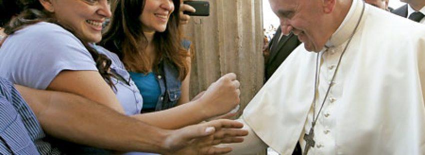 papa Francisco con una mujer embarazada bendiciéndo al bebé en su vientre