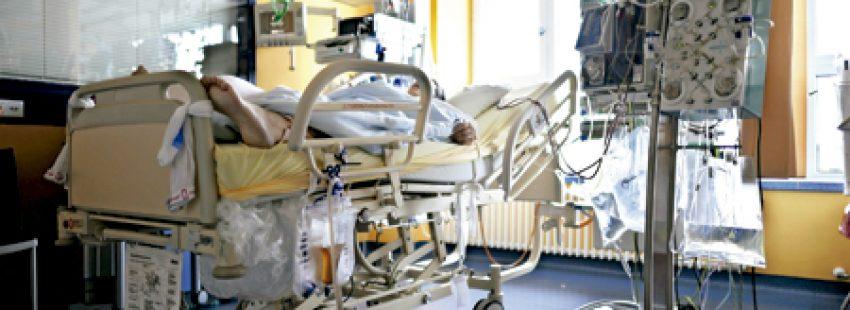 paciente enfermo en una cama de hospital conectado a varios aparatos