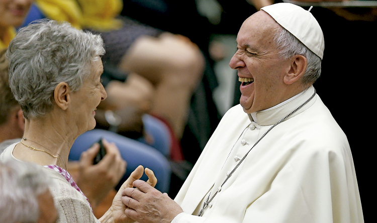 papa Francisco saluda y se ríe con una mujer mayor durante una audiencia