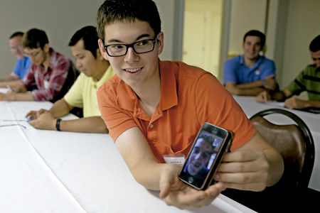 varios seminaristas jóvenes en clase con un teléfono móvil