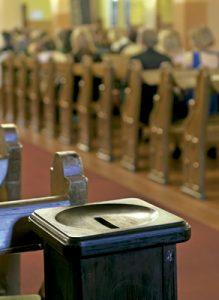 cepillo donde depositar dinero donado en una iglesia