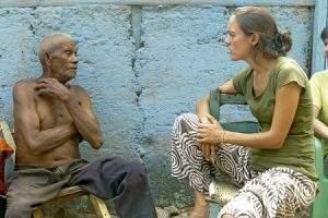 chica joven misionera laica en República Dominicana hablando con un hombre mayor