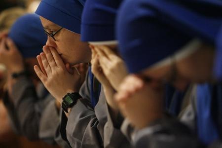 religiosas rezando jóvenes arrodilladas con las manos en la cara