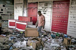 joven en una tienda destrozada por la violencia postelectoral tras los comicios de diciembre 2016 cuando ganó el opositor frente a la dictadura