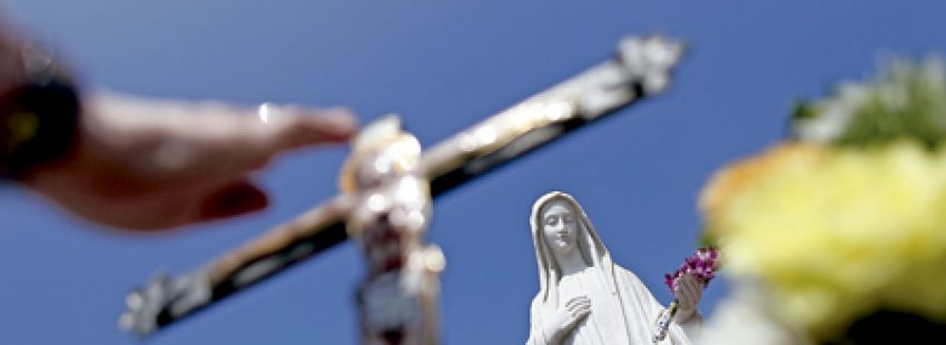 mano rezando hacia una figura de la Virgen en el santuario de Medjugorje Bosnia-Herzegovina