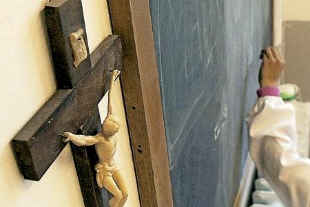 crucifijo en el aula en una escuela una niña escribe en la pizarra