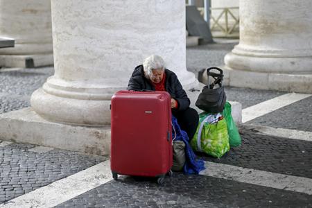 mujer sin techo con maleta y bolsas espera a otra persona en la Plaza de San Pedro del Vaticano