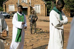 sacerdotes y soldado francés junto a una catedral en República Centrofricana