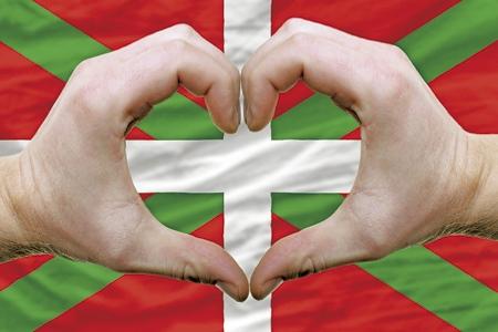 manos formando un corazón sobre una bandera del País Vasco