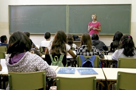 profesora en el aula en un colegio dando clase a alumnos estudiantes