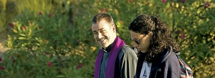 sacerdote camina al lado de una chica joven acompañamiento