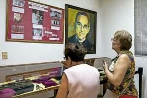 dos señoras rezan y visitan una exposición sobre beato Óscar Romero