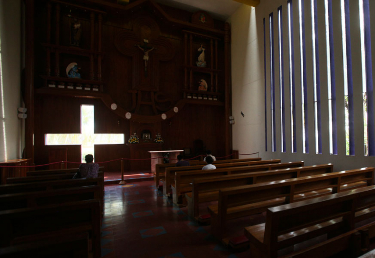 Una iglesia casi vacía en la que algunas personas rezan archivo