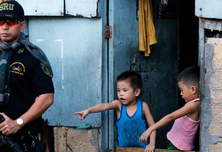 Un policía vigila vivienda en Filipinas durante operación antiidroga. Dos niños le observan