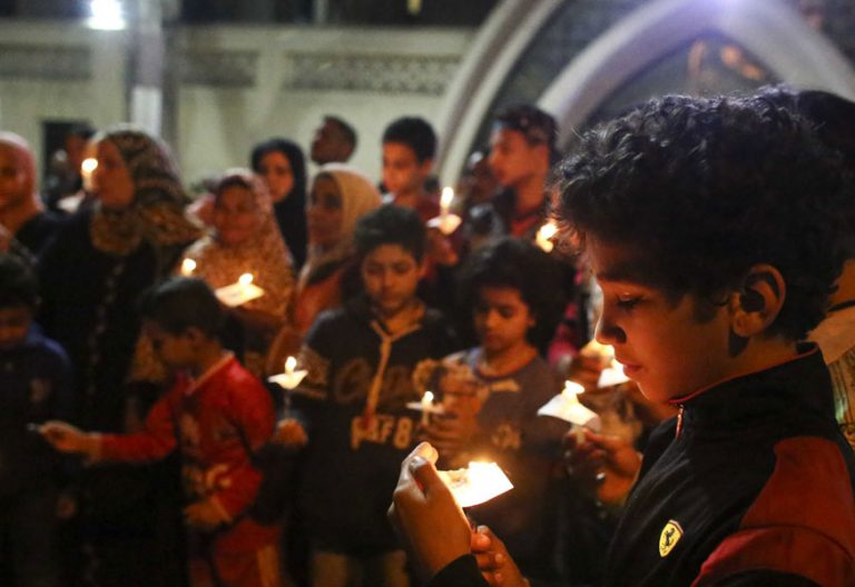 jóvenes niños y adultos en Egipto rezan por las víctimas del ataque terrorista contra una iglesia cristiana en abril