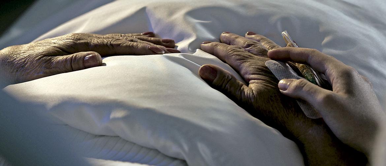 manos de mujer anciana en la cama con una enfermera que le pone una medicación