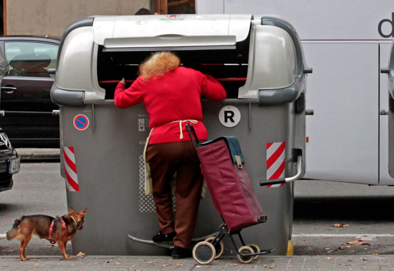 Una mujer pobre busca comida en un contenedor de basura en Barcelona