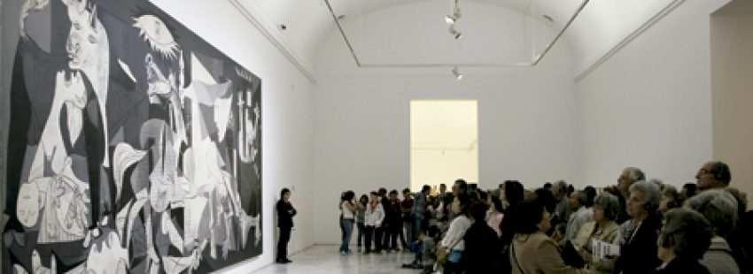 grupo de gente visitantes observan el Guernica cuadro de Picasso en el Museo Reina Sofía