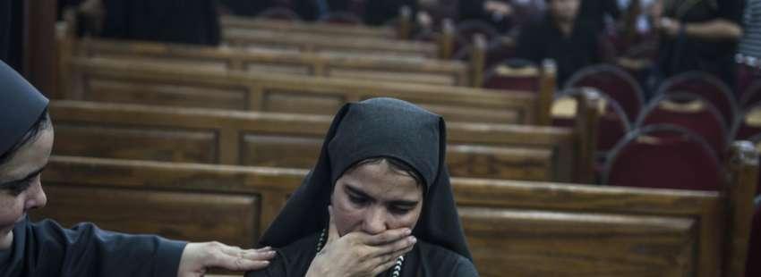 Una mujer llora mientras es consolada durante el funeral de las víctimas de un atentado perpetrado en la entrada del Monasterio de San Samuel el Confesor 26 mayo 2017