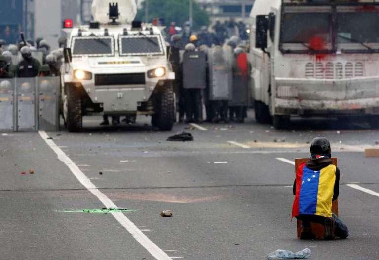 Un joven se enfrenta a los carros de la policía en Caracas