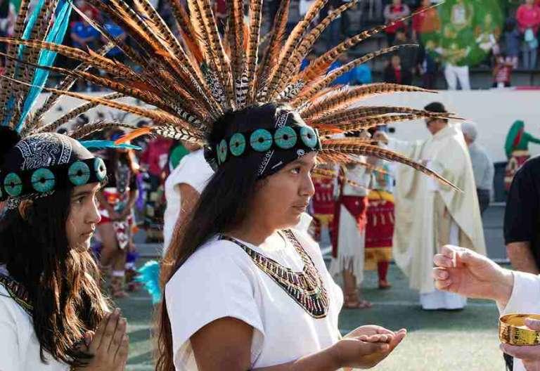 dos chicas jóvenes se acercan a comulgar recibir sacramento eucaristía indígenas durante una celebración