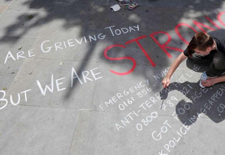 Manchester atentado terrorista un joven pinta en el suelo un mensaje de ánimo para víctimas y familiares ataque Inglaterra 22 mayo 2017