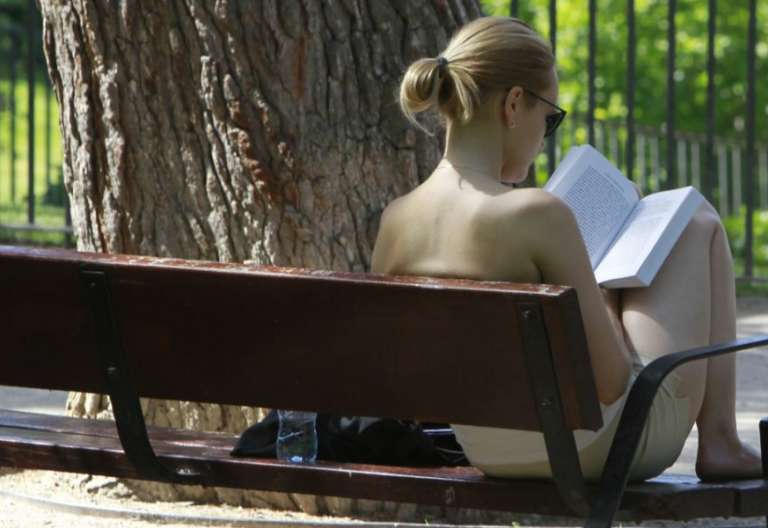 Mujer, en un banco de un parque leyendo /EFE
