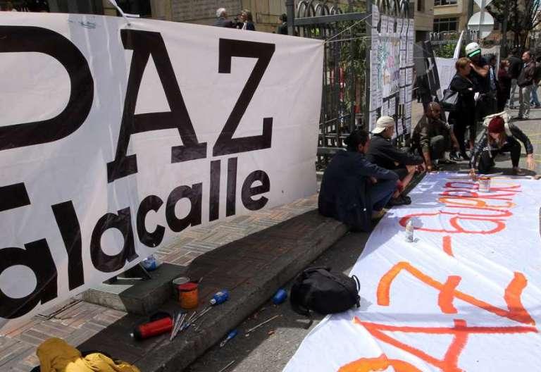 carteles pidiendo paz manifestantes preparando una marcha en Colombia