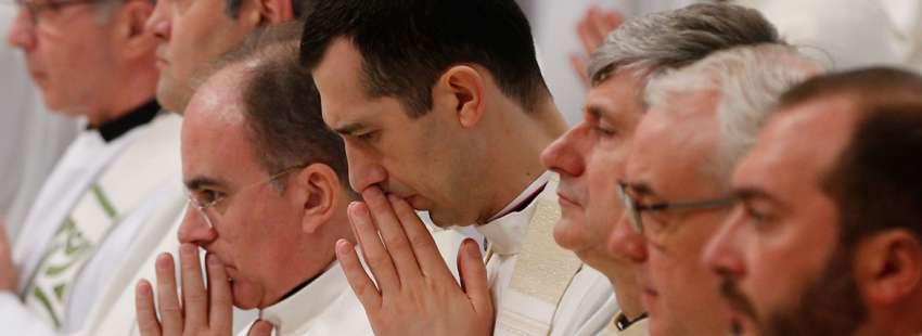 grupo de sacerdotes en una celebración misa rezando en silencio